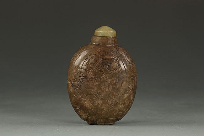 A CHINESE JADE SNUFF BOTTLE WITH CARVINGS