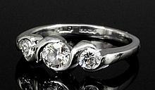 A modern platinum mounted three stone diamond ring by Dominic Walmsley, the
