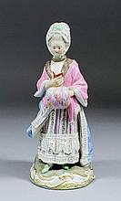 A 19th Century Meissen porcelain standing figure of a woman in 18th Century