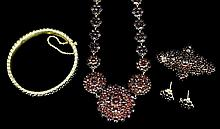 A late Victorian gold coloured metal mounted garnet set suite of jewellery,