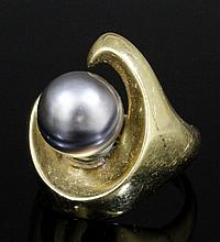 A modern 14k gold mounted black pearl ring, the stylised comma pattern face