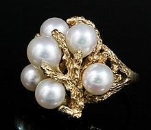 A modern gold coloured metal mounted pearl set ring, the textured seaweed p