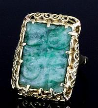 An early 20th Century gold coloured metal mounted jade set ring, the oblong