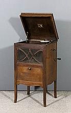 A H.M.V. oak cased gramophone with fretted and mesh speaker, panelled fall-