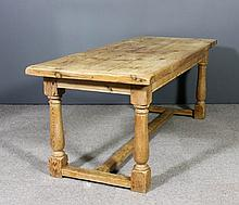An old stripped pine refectory table with cleated three plank top, on balus
