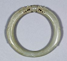 A Chinese pale celadon jade bangle carved with two dragons heads supporting