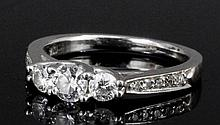 A modern 18ct white gold and platinum mounted three stone diamond ring, the