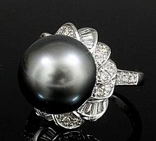 A modern 18ct white gold, black pearl and diamond set ring, the 12mm black