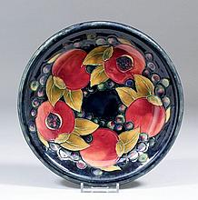 """A Moorcroft pottery plate, tube lined with """"Pomegranate"""" design on a deep m"""