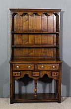 A small Titchmarsh & Goodwin oak dresser, the upper part with moulded corni