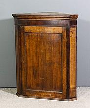 A late Georgian oak and mahogany banded hanging corner cupboard with moulde