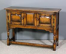 A panelled oak low sideboard in the manner of Titchmarsh & Goodwin, enclose