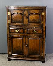 A panelled oak cupboard in the manner of Titchmarsh & Goodwin, the upper pa