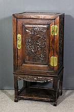 A Chinese rosewood panelled dwarf cupboard, enclosed by single door carved