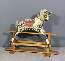 An early 20th Century dapple grey rocking horse by Collinson, with stand fo