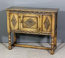 """A panelled oak side cupboard of """"17th Century"""" design with carved rails, en"""