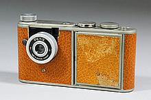 A Petie tinplate and brown leatherette camera compact, the front of the bod