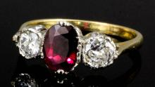 A modern gold and silvery coloured metal mounted ruby and diamond three stone ring, the oval cut ruby approximately 1.25ct shouldered by two brilliant cut diamonds each approximately .33ct (gross weight 3.6 grammes - ring size O)