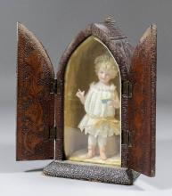 A 19th Century German bisque porcelain and lace figure of a standing girl holding a book, 6.75ins high, contained in poker work box of lancet pattern, 5.25ins x 4.75ins x 8.5ins high