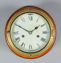An early 20th Century brass cased ship's bulkhead clock, the 6ins diameter white painted metal dial with Roman numerals to the eight day two train movement striking the