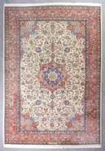 A Sarouk carpet woven in muted colours with a bold circular central medallion, the field filled with trailing leaf and floral ornament, on an ivory ground within seven stripe borders filled with trailing leaf and floral ornament, and with signed panel to top edge, 9ft 6ins x 6ft 9ins