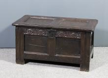 A small 17th Century panelled oak coffer with two fielded panels and moulded edge to lid, the frieze carved with lunette ornament above fielded panels, 31ins x 14.75ins x 16.75ins high (splits to some panels)