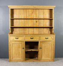 A Victorian stripped pine kitchen dresser, the upper part with moulded cornice, fitted two open shelves, the base fitted three frieze drawers, central open niche under flanked by cupboards enclosed by panelled doors, on plinth bas, 71ins wide x 15ins deep x 82ins high