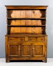 An 18th Century panelled oak dresser, the upper part with moulded cornice, fitted two open shelves with shaped sides, the base fitted two frieze drawers above cupboards enclosed by fixed centre panel and flanked by a pair of fielded panelled doors, 51ins wide x 18ins deep x 68.5ins high (top probably rebuilt and reduced in height)
