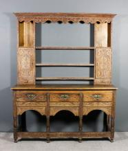 A 19th Century oak dresser, the whole later carved with leaf scroll and floral ornament, the upper part with moulded cornice, shaped frieze, fitted five open shelves and cupboards enclosed by single doors with drawers under, the base fitted three frieze drawers, on turned legs, 65.5ins wide x 21.5ins deep x 81ins high (top of the base section loose and not fixed down and has old repairs)