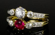 A modern 18ct gold mounted twin band ruby and diamond set ring, the central brilliant cut diamond (a
