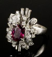 A modern 18k white gold ruby and diamond set flowerhead pattern ring, the central oval cut ruby appr