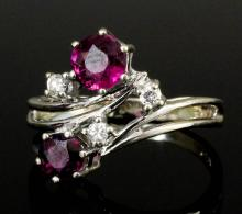 A modern 14ct white gold ruby and diamond crossover pattern ring, the two circular cut rubies .33ct