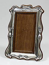 An Edward VII silver photograph frame, with shaped