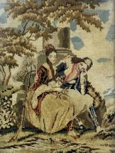 A Victorian needlework panel worked in coloured wools of a young man and a woman beside a pillar in