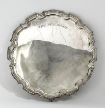 A George V silver circular salver with moulded piecrust rim and on three cl