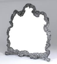 A late Victorian silver framed dressing table mirror of shaped outline, the