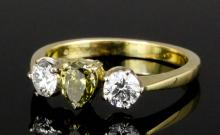 A modern 18ct gold mounted chameleon diamond three stone ring, the central