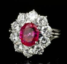 A modern silvery coloured metal mounted ruby and diamond ring, the oval cut