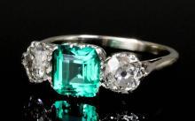 A modern silvery coloured metal mounted emerald and diamond three stone rin