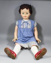 A display doll with closing eyes, in blue and printed dress, 35ins long, an