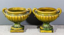 A pair of green glazed pottery two garden urns with leaf scroll handles and