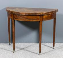 A George III mahogany semi-circular card table with crossbanded baize lined