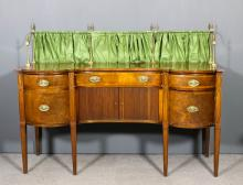 A George III mahogany sideboard of shaped outline, the top with brass galle