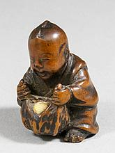 A Japanese boxwood netsuke, carved in the form of a seated boy opening fruit, 1.5ins (37mm) high, un