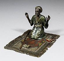 A late 19th/early 20th Century Austrian cold painted bronze figure of a praying Arab on a carpet wit