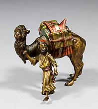 An early 20th Century Austrian cold painted bronze figure leading a laden camel, 3ins high x 3.25ins