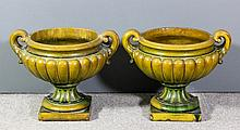 A pair of green glazed pottery two garden urns wit