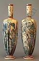 A good pair of Martinware saltglazed stoneware vases of slender baluster form with narrow cylindrical necks, the bodies finely incised and decorated in green and blue with irises, dragonflies and other flowers, on incised circular bases, 13.5ins high