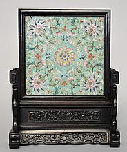 A Chinese wooden table screen with porcelain panel,turquoise ground, famille rose decorated with floral motifs, 19thC, H 36,22,5 x 22,5 cm (scratches and parts of the stand missing)