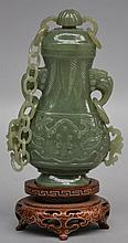 A Chinese carved green jade vase with cover on a wooden base, H 16,5 cm